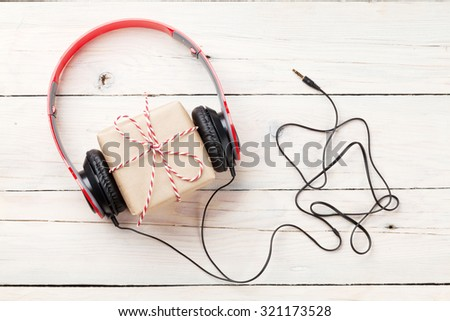 Gift box with headphones on wooden table. Top viw - stock photo