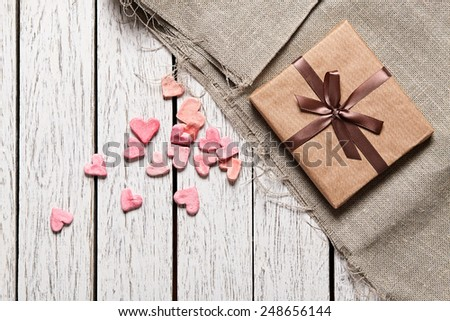 Gift box with heap of small hearts on white wood table. - stock photo