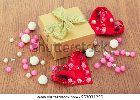 gift box with hearts and beads on wooden background