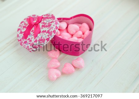Gift box with hearts on a white wooden background. Valentine's Day. Card