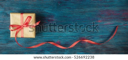 Gift box with long ribbon over blue rustic background