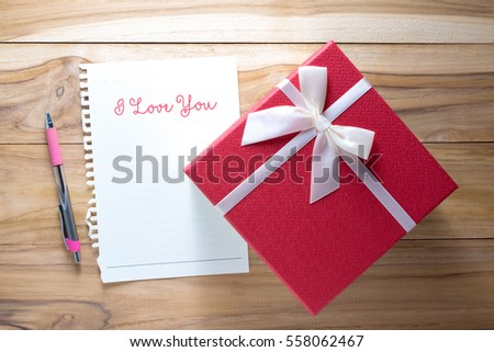 Gift box with paper card and white ribbon. Valentines day symbols on a wood background. I Love You.