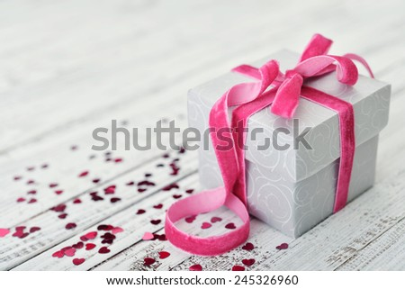 Gift box with pink bow and confetti in shape of heart on wooden background - stock photo