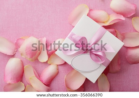 gift box with pink ribbon bow and rose petals - stock photo