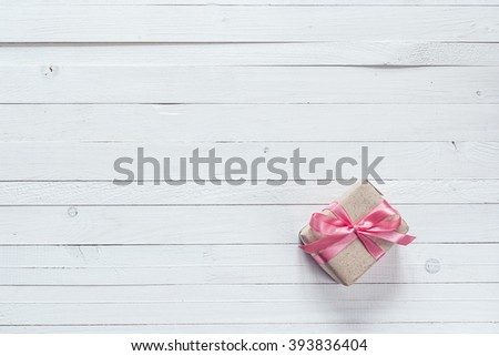 Gift box with pink ribbon on white painted wooden planks and empty space for text. Top view with copy space - stock photo