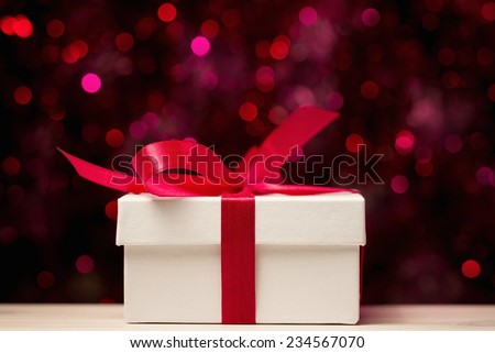 Gift box with red bow against defocused lights - stock photo