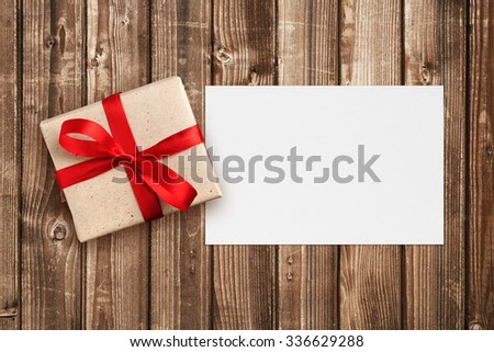 Gift box with red bow and blank greeting card - stock photo