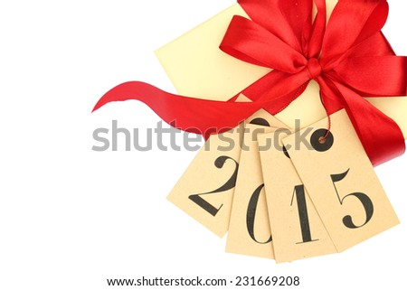 Gift box with red bow and tags with new year 2015 isolated on white - stock photo