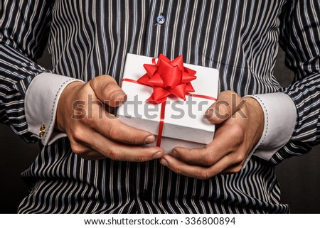 Gift box with red bow in man's arms. - stock photo
