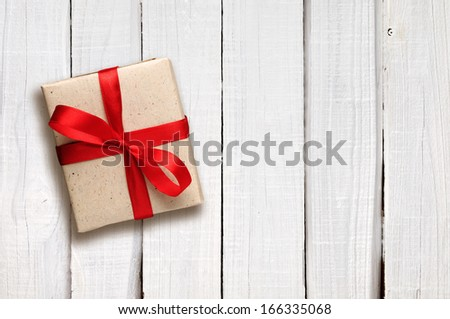 Gift box with red bow on white wooden background - stock photo