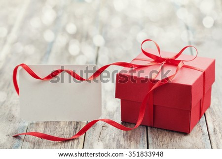 Gift box with red bow ribbon and empty paper note on wooden table for Valentines day - stock photo
