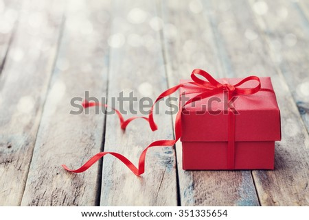 Gift box with red bow ribbon on wooden table for Valentines day, vintage toned - stock photo