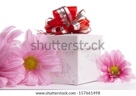 Gift-box with red bow with pink daisies over white - stock photo