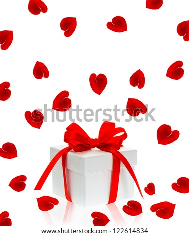 gift box with red ribbon bow and rose flower petals in hearth shape over white background - stock photo