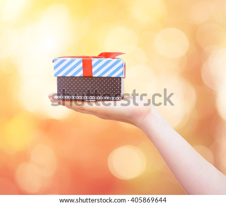 gift box with red ribbon in hand on nature background with color tone effect - stock photo