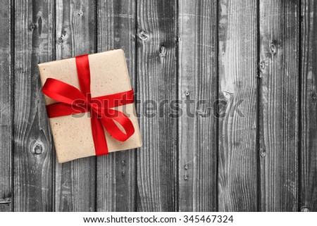 Gift box with red ribbon on black and white wooden background - stock photo