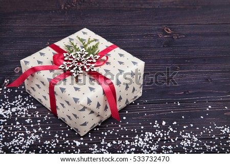 gift box with red ribbon on wood background with space