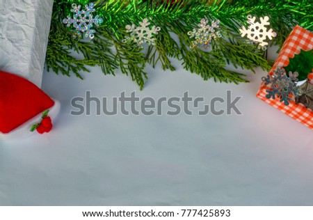 Gift Box with red stripes, colored balls, Santa Claus Red Hat, Juniperus Chinensis green on a white background. for use as a card.Christmas day concept.