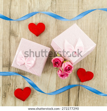 Gift box with rose flower, heart and ribbon on wooden background