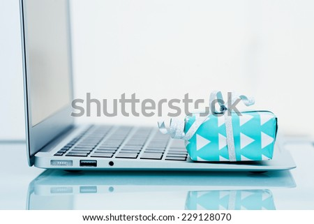 Gift box with silver bow on light background next to the computer. On line shopping