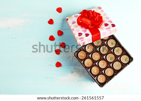 Gift box with tasty chocolate candies on wooden table