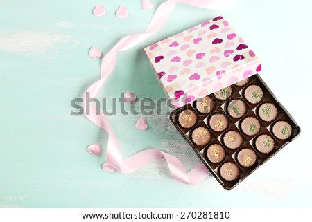 Gift box with tasty chocolate candies on wooden table - stock photo