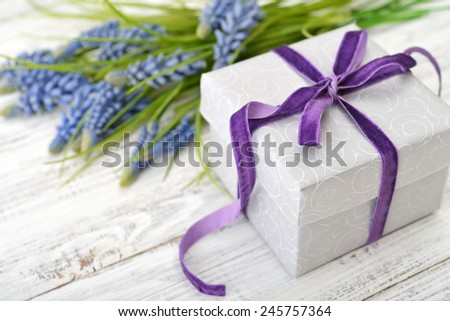 Gift box with violet ribbon and bouquet of hyacinth on wooden background - stock photo