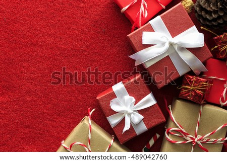 Gift box with white ribbon on red velvet background. over light and high contrast