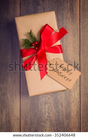 Gift box wrapped and tied with red ribbon with Happy Holidays tag