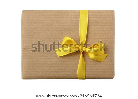 Gift box wrapped in natural paper and decorated with simple vertical yellow bow - top view - isolated on white - stock photo