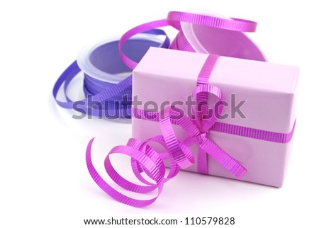 Gift box wrapped in pink wrapping paper and purple curly ribbon isolated on white background. - stock photo