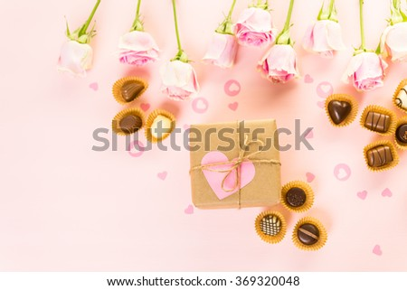 Gift box wrapped in recycled paper and decorated with pink heart with pink roses. - stock photo