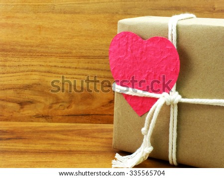 gift box wrapped in recycled paper with white rope and pink heart paper tag - stock photo
