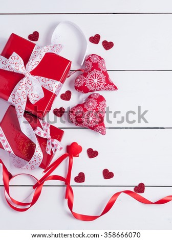 Gift box wrapped with a ribbon. Little red hearts on white wooden background.Valentine's day background.