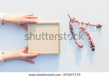 Gift box wrapping step by step. Woman packs gift on white background at sunset. - stock photo