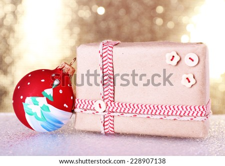 Gift boxes and Christmas tree toy on table on shiny background - stock photo
