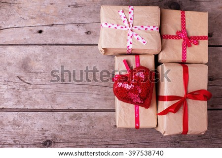 Gift boxes and red decorative heart  on  vintage wooden background. Selective focus. Place for text. - stock photo