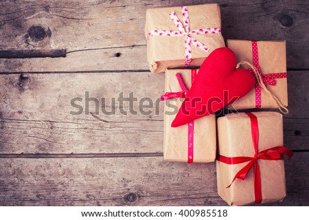 Gift boxes and red decorative heart  on  vintage wooden background. Selective focus. Place for text. Toned image. - stock photo
