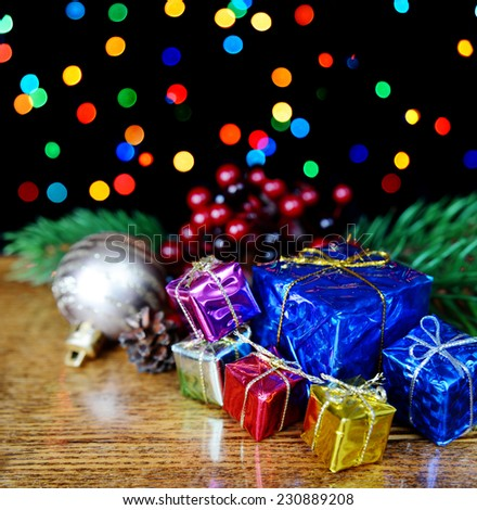 Gift boxes and spruce branches against a background of colored lights