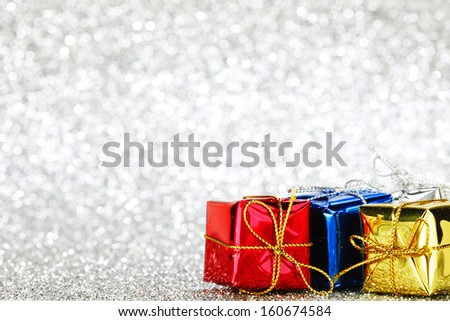 Gift boxes on glitter silver background