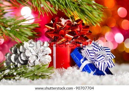gift boxes on snow with christmas tree branch on blurred background