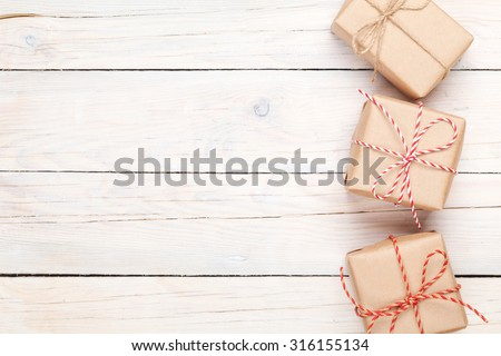 Gift boxes on white wooden table background with copy space - stock photo