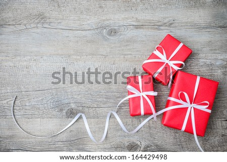 Gift boxes with bow on wooden background - stock photo