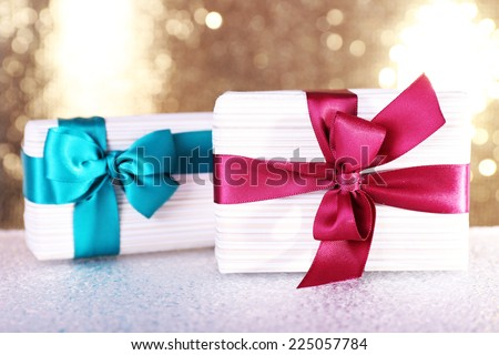 Gift boxes with vinous and blue ribbons and Christmas toy on table on shiny background - stock photo