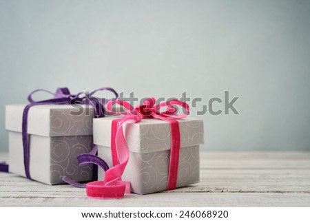 Gift boxes with violet and pink ribbons on blue background - stock photo