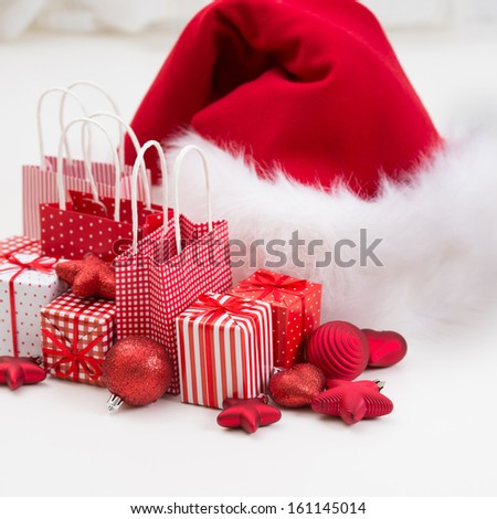 Gift boxes with xmas presents wrapped in red paper with ornament and Christmas decorations on white background - stock photo