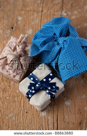 Gift boxes wrapped in rustic fabric - idea for Christmas or Birthday from above - stock photo