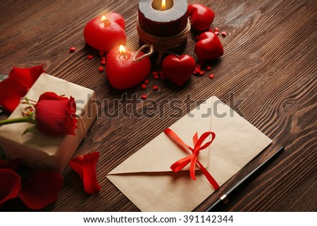 Gift card for Valentine's Day with pen and candles on wooden background