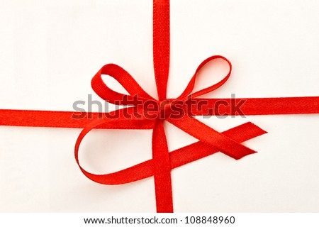 gift card with red ribbon on creme textured background - stock photo