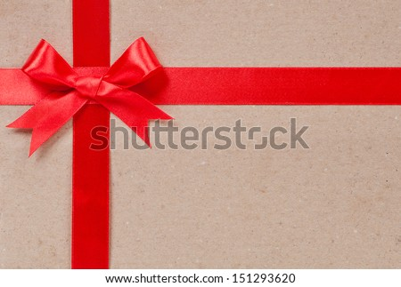 Gift concept - Red bow and ribbon on cardboard